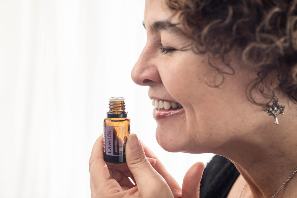 woman smelling do terra essential oils in photo session